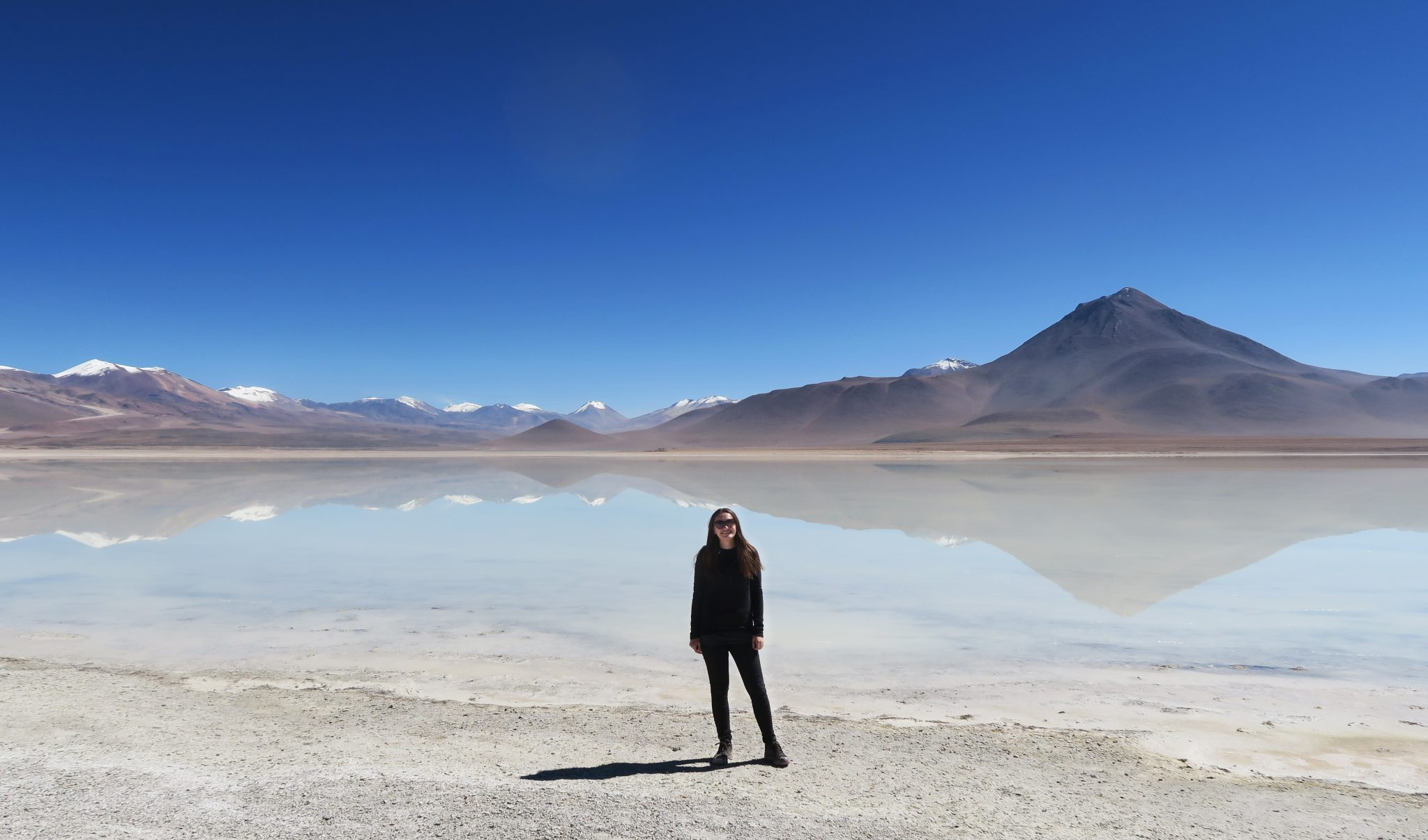 Girl standing by lagoon in Uyuni, Bolivia