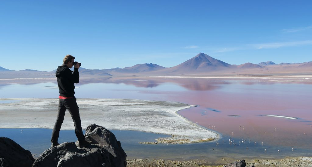 Man taking photo of lagoon, Uyuni, Bolivia