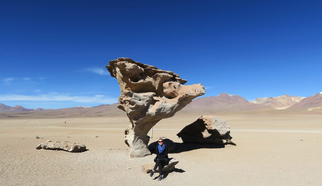 Girl sitting by stone tree, Uyuni, Bolivia