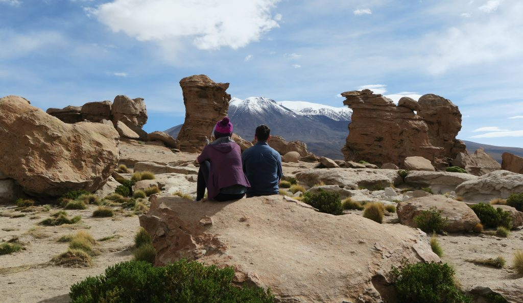 Couple sitting on rock formation in Uyuni, Bolivia