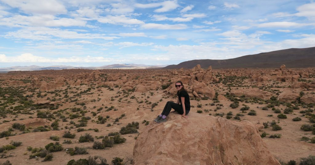 Girl sitting on rock formation in Uyuni, Bolivia