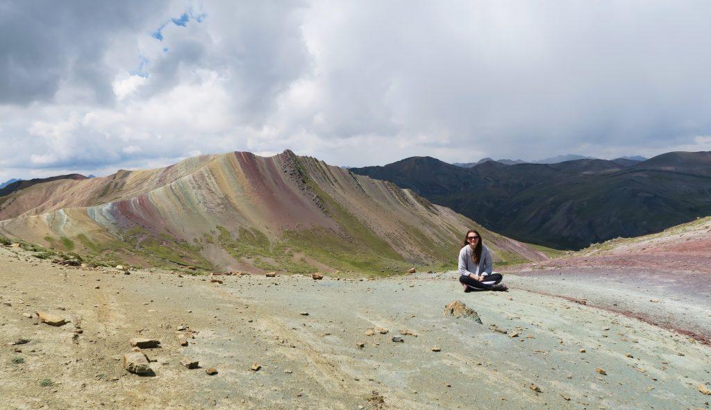 Girl sat on Palcoyo Rainbow Mountain